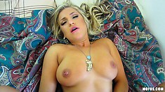 Lying on the bed, the busty babe gets fucked deep and moans with intense pleasure