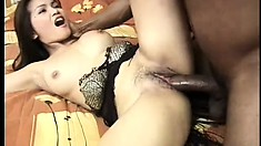 The Oriental cutie lies on the bed and the black stud fucks her tight pussy deep