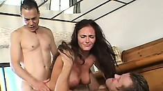Slutty brunette broad pleasures a pair of big dicks with gusto