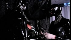 Two lovers do extreme BDSM session with full leather bodysuits on